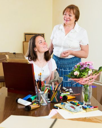 the elderly tutor: Smiling mentor assesses the work of his happy student Stock Photo