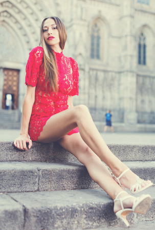 portrait of young positive american adult girl in evening apparel sitting in european town Stock Photo