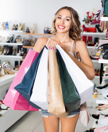 Portrait of smiling woman which is showing purchases in shoes store. Stock Photo