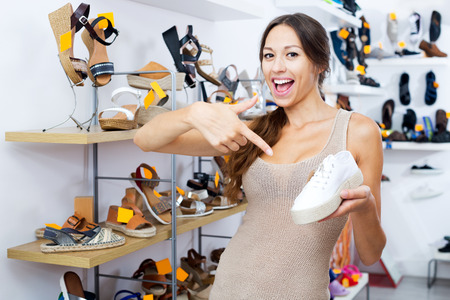 Attractive young female customer showing desired shoe in boutique