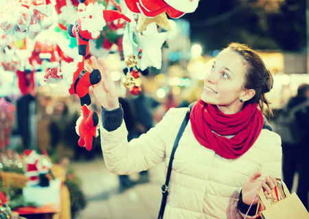 Portrait of happy female customer at Christmas fair in evening  Stock Photo