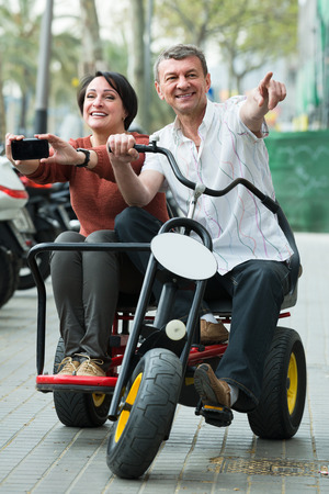 american couple driving double bike outside and making photos