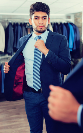 Man is trying on jacket in front of the mirror in store
