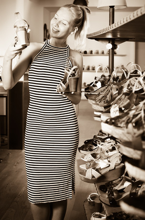 Glad woman choosing and comparing two pairs of new shoes in shop Stock Photo
