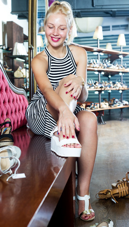 Portrait of young pretty woman fitting picked footwear in fashion boutique Stock Photo
