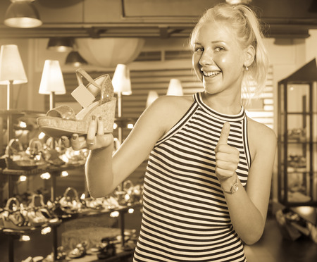 Laughing woman shopaholic holding desired shoe in fashion boutique