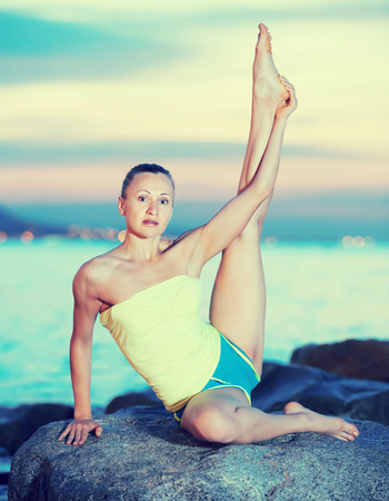 Young sporty female doing aerobics at ocean quay Stock Photo
