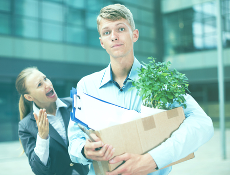 Angry businesswoman is chastising  the employee for violating the job description outdoors. Stock Photo