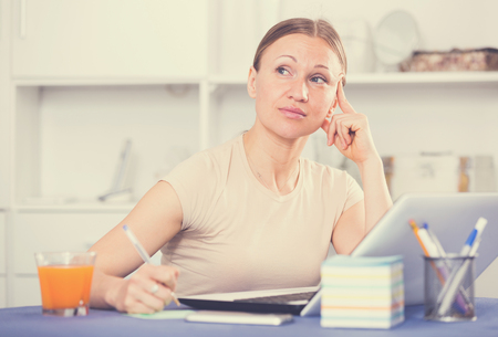 Young woman with pen in hand dreaming while working on laptop