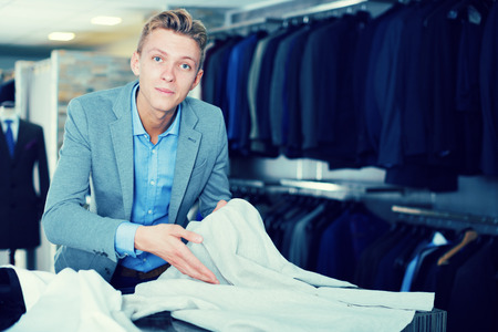 Adult male purchaser in jacket choosing shirt in the clothes store Stock Photo