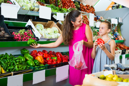 woman and little girl taking red and green paprika on fruit market Stock Photo