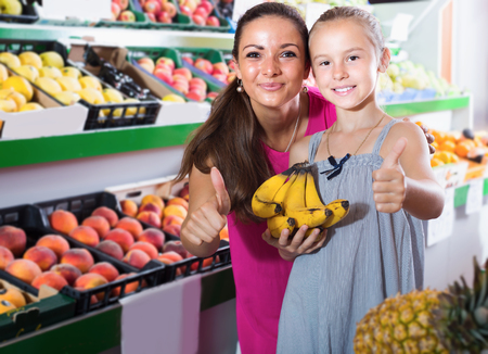 Smiling young female with girl looking satisfied and holding thumbs up  in supermarket