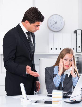 tardiness: Businessman feeling angry to female coworker at workplace in office