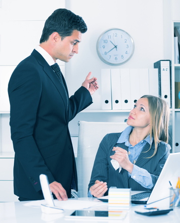 tardiness: Dissatisfied manager scolding frustrated female assistant in office Stock Photo