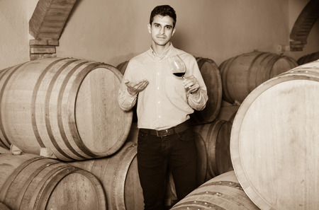 Cheerful  male customer tasting red wine from wooden barrels in factory Stock Photo