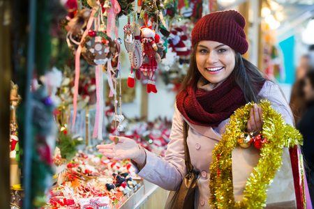 overspending: Portrait of cheerful smiling girl choosing Christmas decoration at market Stock Photo