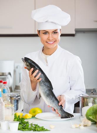 jorobado: Chef holding carcass of rainbow trout in professional kitchen Foto de archivo