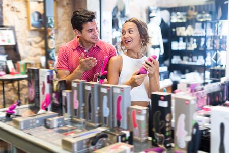 섹스 샵에서 섹시한 장난감을 들고 행복한 여자와 남자 소비자의 초상 스톡 콘텐츠