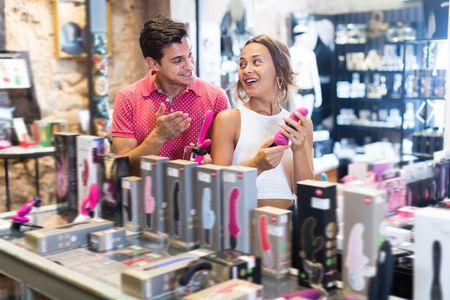 Portrait of happy girl and man consumers holding sexy toys in the sex shop