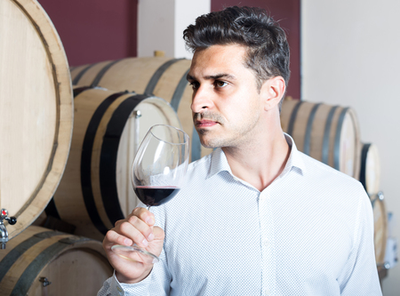 look latino: portrait of positive man tasting wine sample in glass in alcohol section with woods