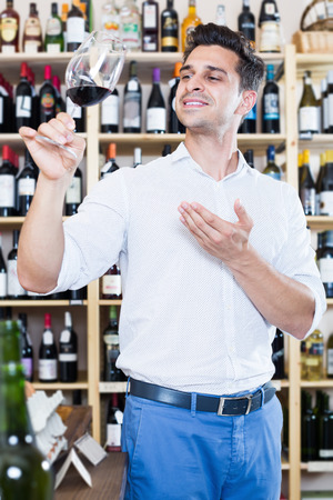Cheerful man holding glass of red wine in winery section in store