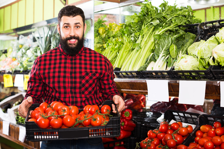 Happy adult shop assistant demonstrating tomatoes in grocery shop