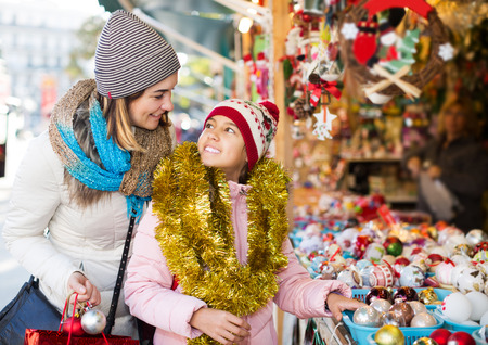 overspending: Smiling little girl with happy mom buying decorations for Xmas. Focus on girl Stock Photo