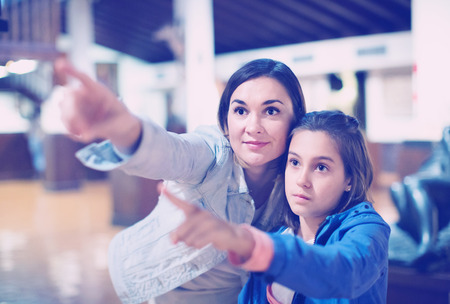 Young glad  mother and daughter enjoying expositions of previous centuries in museum