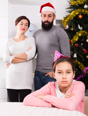 Father and mother telling off their daughter for disobedience at Christmas Stock Photo