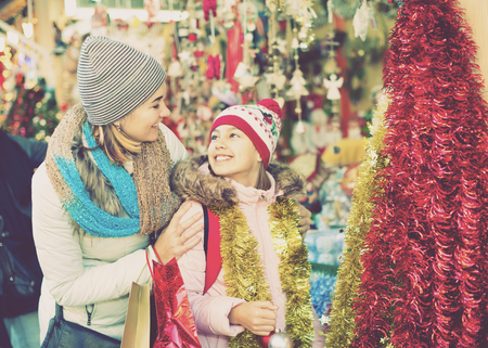 Pleasant smiling female customers staring at counter of Christmas market. Focus on woman Stock Photo