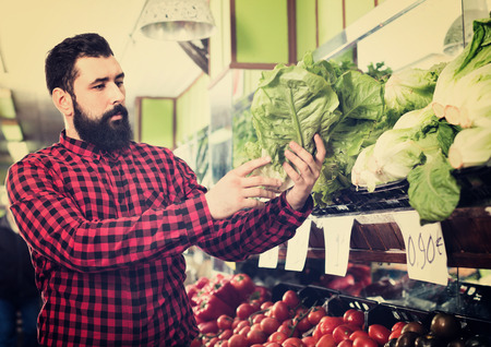 sorts: Young glad cheerful male seller offering salad in grocery shop