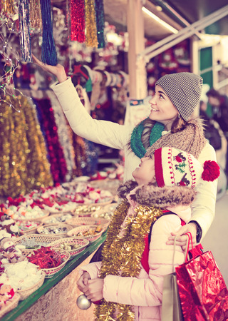 consumerism: Happy little girl with mom buying decorations for Xmas. Focus on woman Stock Photo