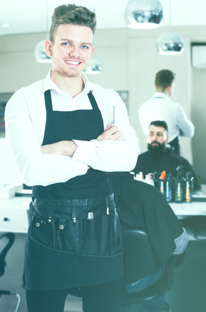 Young guy displaying his workplace and tools at hairdressing salon