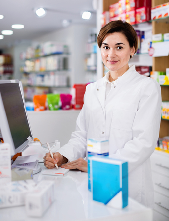 Young  friendly smiling female pharmacist offering help in choosing at counter in pharmacy Stock Photo