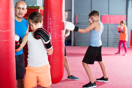 Boy with the trainer earns accuracy of blows on a boxing bag in a sports hall