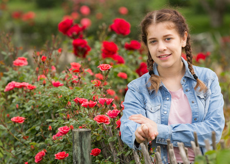young russian  female posing near roses and holding a basket in the garden Stock Photo