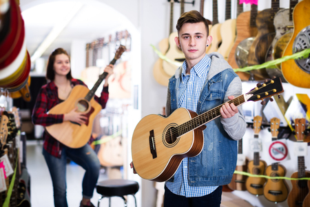 Smiling female and male teenagers choosing acoustic guitars in guitar store Stock Photo