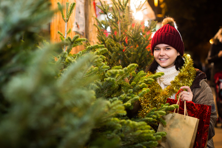 overspending: Glad adult girl staying at market among Christmas trees