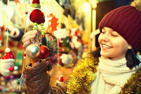 overspending: Smiling positive teenage girl shopping at festive fair before Xmas