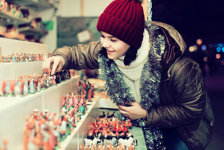 creche: russian smiling female teenage customers staring at counter of kiosk with figures for creating  miniature Christmas scenes   Stock Photo