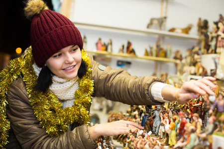 creche: Smiling girl  buying figures and workpiece for creating Christmas  Stock Photo