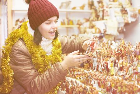 creche: Happy girl  buying figures and workpiece for creating Christmas Stock Photo
