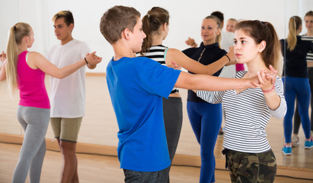 Group of cheerful american teen dancing salsa in dance studio