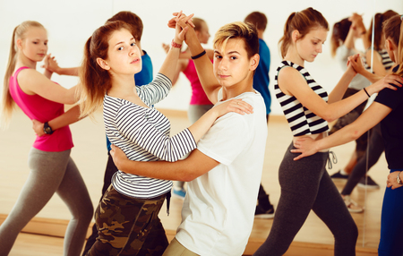 Group of energy teenagers trying dancing with partner in classroom