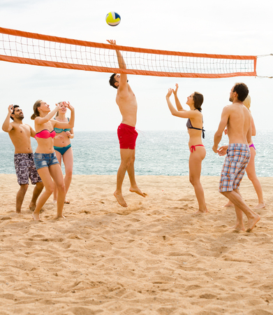 Glückliche Erwachsene im Urlaub, die mit einem Ball auf einem Strand nahe Ozean spielen