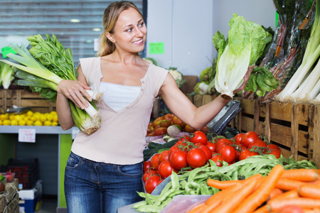 Portrait of young glad cheerful woman shopping fresh green celery, leek and lettuce in shop
