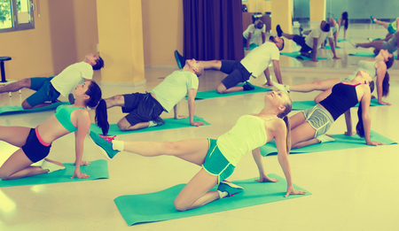 Yoga in studio, group of happy people  practicing healthy lifestyle