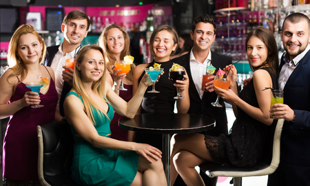 Cheerful young females and smiling males celebrating corporate in the bar at night