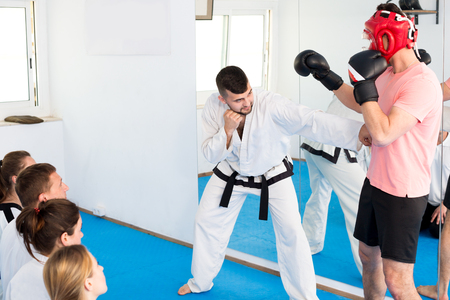 Cheerful male coach explaining painful hold to adults in taekwondo class