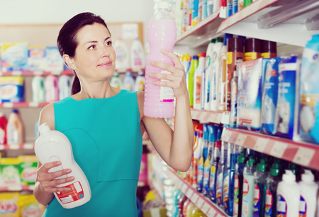 lavar platos: Beautiful female in the shop want to buying cleaners in bottle